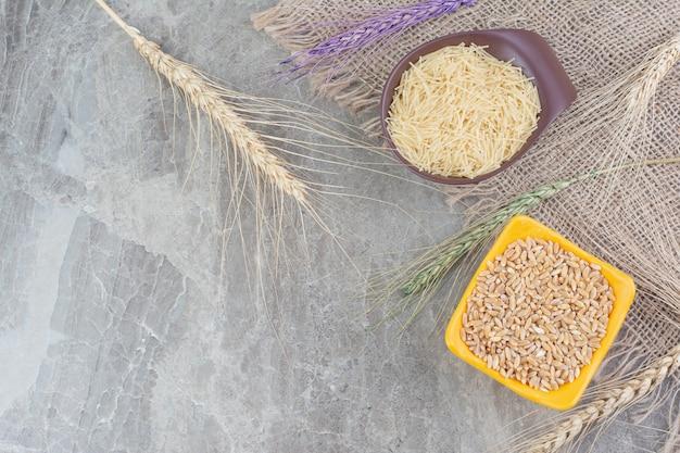 Tarwekorrels en rijstdeegwaren in ceramische kopjes