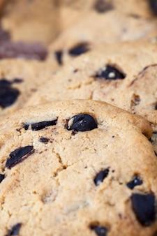 Tarwemeelkoekjes en grote stukken zoete chocolade samen, koekjes met chocoladestukjes in close-up,