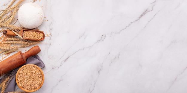 Tarweoren en tarwekorrels opgezet op marmeren achtergrond. bovenaanzicht en kopieerruimte