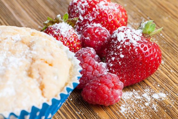 Tarwezoete cake en een rijpe sappige aardbei, bestrooid met zoet suikerpoeder
