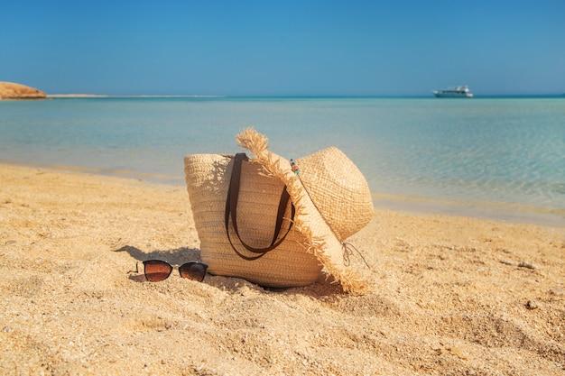 Tas en hoed op het strand in de buurt van de zee.