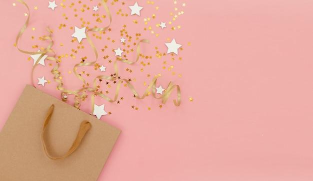 Tas met confetti, cadeautjes en strikken, horizontale bovenaanzicht. nieuwjaar en kerstmis feestelijke achtergrond. vakantie, winkelen en verkoop concept.