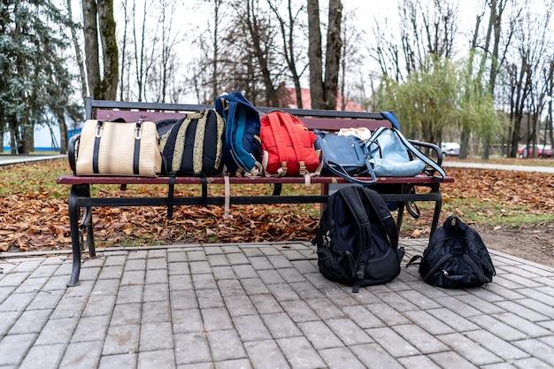 Tassen en rugzakken liggen op een parkbank.