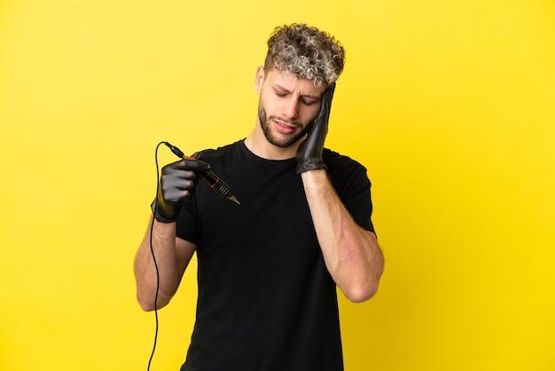 Tatoeëerder blanke man geïsoleerd op gele achtergrond met hoofdpijn