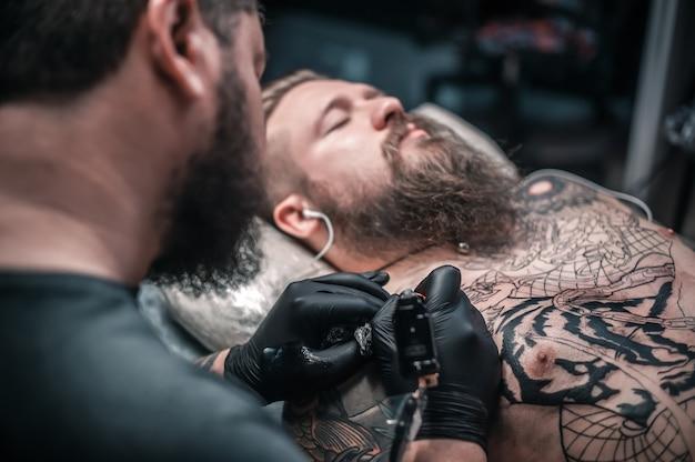 Tatoeëerder demonstreert het proces van het krijgen van een tatoeage in de salon