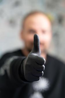 Tatoeëerder die zwarte latexhandschoenen draagt die duimen opdagen