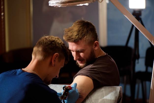 Tatoeëerder maakt een tatoeage op de hand van een man.