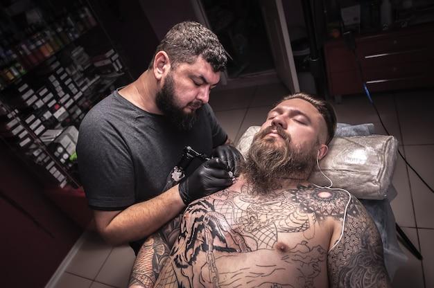 Tatoeëerder maakt een tatoeage op de huid in de tattoo-studio
