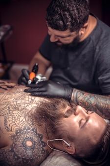 Tatoeëerder maakt een tatoeage op de studio van zijn cliënt.