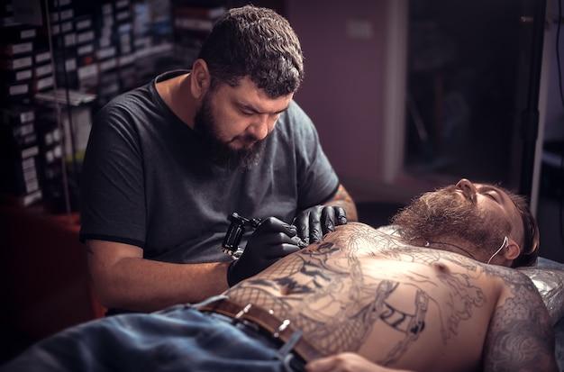Tatoeëerder poseren in tattoo studio