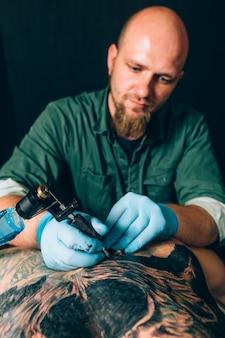 Tattoo meester kunstenaar maakt een tatoeage. detailopname