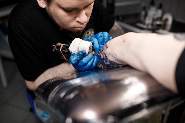 Tattoo meester op het werk maakt tekenen bij de hand