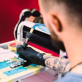 Tattoo meester vulmachine met inkt
