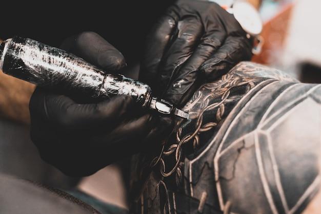 Tattoo salon. de tattoo-meester tatoeëert een man op zijn schouder. tattoo machine, veiligheid en hygiëne op het werk. close-up, getint, tatoeëerder