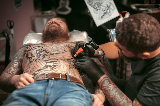 Tattoo specialist maakt een tatoeage in een tattooshop