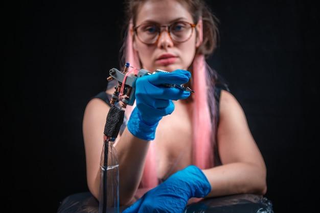 Tattoo-specialist poseert in een tattoo-studio.