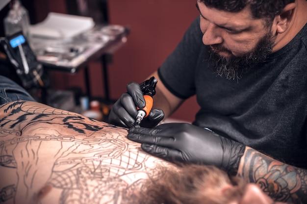 Tattooer bezig met professionele tattoo machinegeweer in tattoo salon.