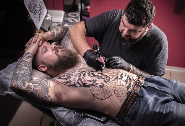 Tattooer doet tatoeage op de huid van zijn cliënt in salon