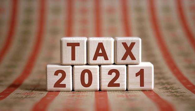 Tax 2021-tekst op houten kubussen op een monochrome achtergrond met reflectie.