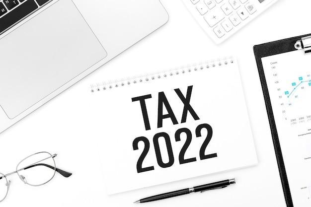 Tax 2022. notitieblok, rekenmachine, grafiek, laptop. boekhoudkundig concept. plat leggen.
