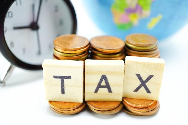 Tax-alfabet met stapel munten en wekker: tijd om te betalen.