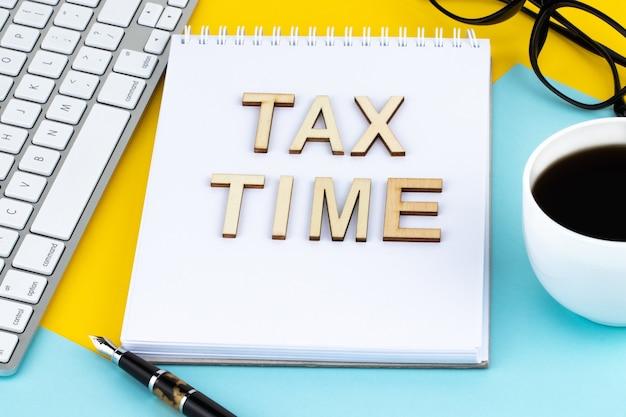 Tax time houten letters met belastingformulier en kopje koffie.