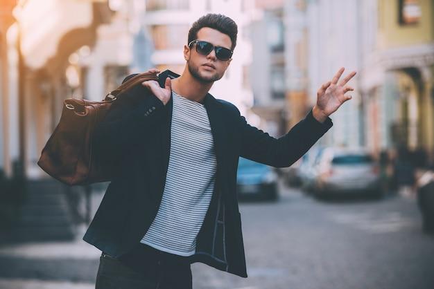 Taxi! knappe jonge man in slimme vrijetijdskleding draagtas op schouder en gebaren tijdens het liften op straat