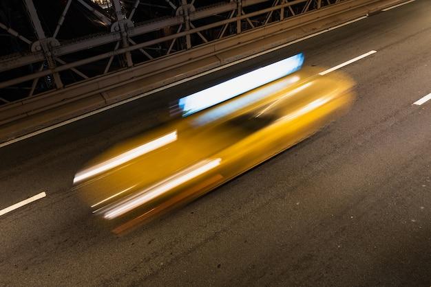 Taxi op brug bij nacht met motieonduidelijk beeld