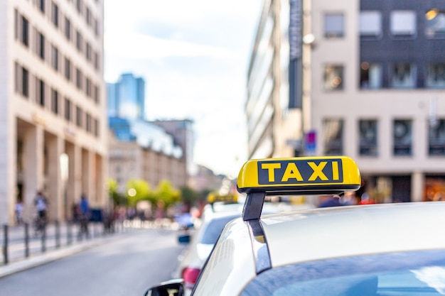 Taxiauto met een geel bord op het dak in de stadsstraten