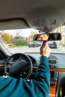 Taxichauffeur kijkt in de spiegel