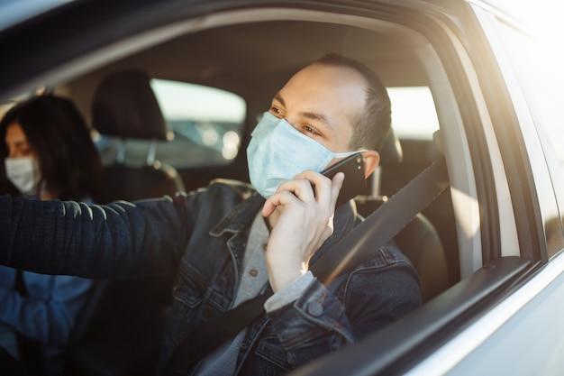 Taxichauffeur praat aan de mobiele telefoon en draagt een steriel medisch masker tijdens het wachten in het verkeer tijdens een coronavirus-pandemie.