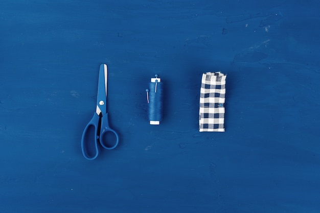 Tayloring-accessoires op klassieke blauwe achtergrond, bovenaanzicht