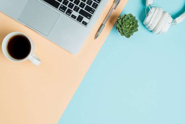 Te en hoofdtelefoons dichtbij laptop