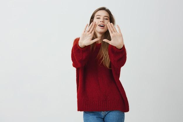 Te goed voor jou. studio shot van emotionele charmante vrouw trekken handpalmen naar camera en kijken met plezier, staande in trendy losse rode trui.