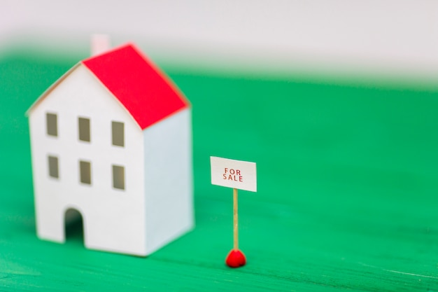 Te koop tag in de buurt van het onscherpe huis model op groene bureau