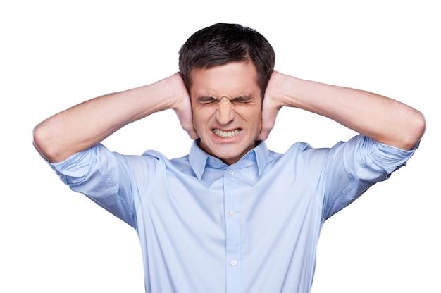Te luid! knappe jonge man in blauw shirt die oren bedekt met handen en grimassen terwijl hij geïsoleerd op wit staat