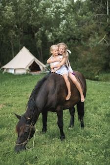 Te paard, twee kinderen meisjes, zussen, paardrijden buiten, glimlachend en knuffelen elkaar