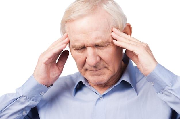 Te stressvolle dag. gefrustreerde senior man in formele kleding die het hoofd met de vingers aanraakt en de ogen gesloten houdt terwijl hij tegen een witte achtergrond staat