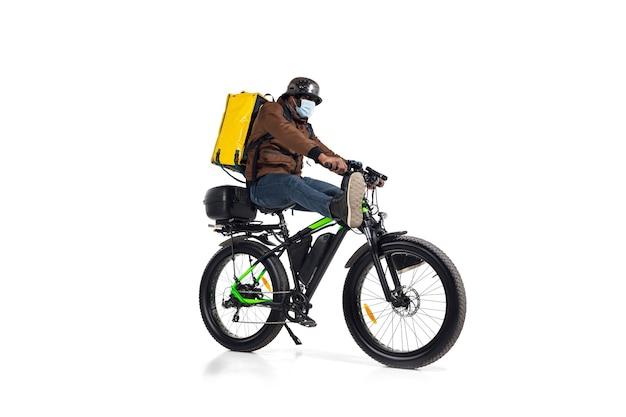 Te veel bestellingen. contactloze bezorgservice tijdens quarantaine. man levert voedsel tijdens isolatie, met helm en gezichtsmasker. eten nemen op de fiets geïsoleerd op een witte muur. veiligheid. opschieten.