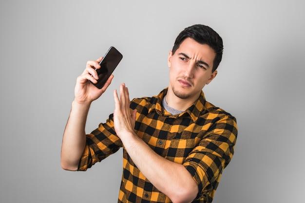 Te veel gepraat. jonge man in geel overhemd geïrriteerd door een stem aan de telefoon, gebarend met één hand