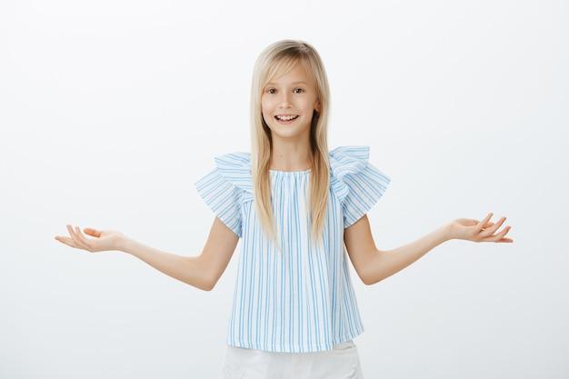 Te veel keuzes voor één kind. portret van clueless verward aantrekkelijk jong blond meisje in blauwe blouse, handpalm spreiden en wegen of schouders ophalen, ondervraagd en zich niet bewust over grijze muur