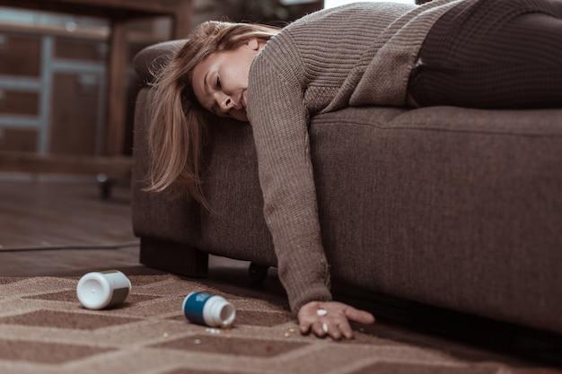 Te veel pillen. blondharige, rijpe familievrouw die in slaap valt na te veel pillen te hebben ingenomen