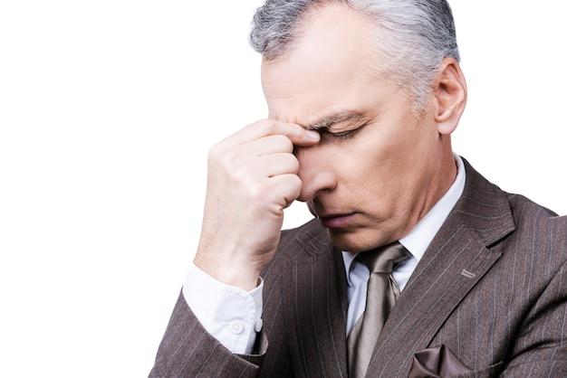 Te veel problemen. gefrustreerde volwassen man in formele kleding die het hoofd met de vingers aanraakt en de ogen gesloten houdt terwijl hij tegen een witte achtergrond staat