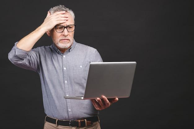 Te veel werk te doen. moe boos senior leeftijd man met laptopcomputer