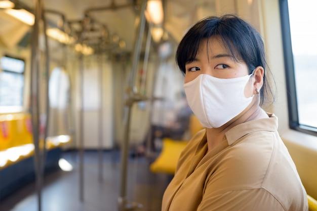 Te zware aziatische vrouw die met masker terwijl het zitten met afstand binnen de trein denken