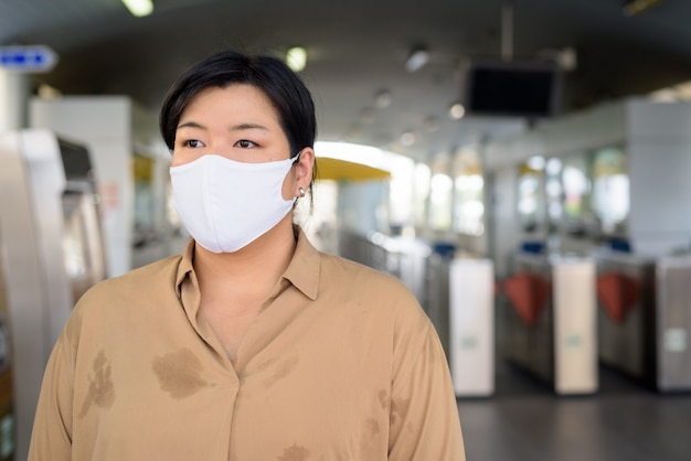 Te zware aziatische vrouw die met masker voor bescherming tegen de uitbraak van het coronavirus denken bij het hemelstation