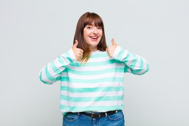 Te zware vrouw die in brede zin gelukkig, positief, zelfverzekerd en succesvol glimlacht, met beide duimen omhoog