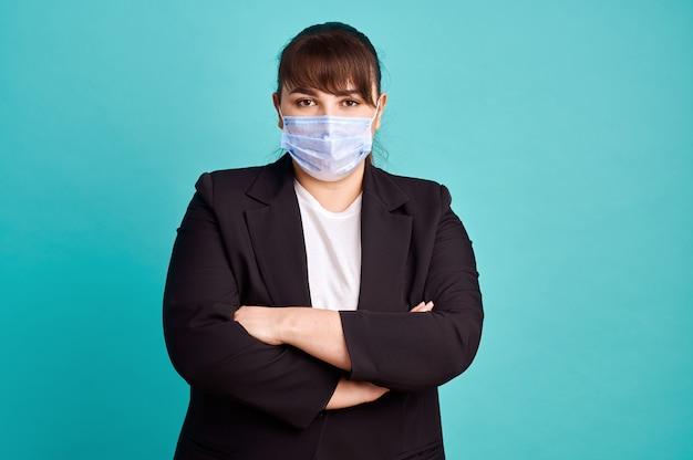 Te zware vrouw in kostuum en medisch masker, lichaams positieve, blauwe muur