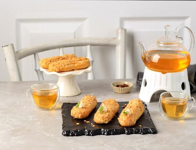 Tea time bakery white concept, theepot en craquelin eclair met kopie ruimte voor tekst
