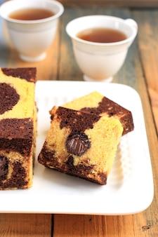Tea time met plakje marmeren reiscake, vierkante cake met gesmolten chocolade in het midden. geserveerd op een wit bord